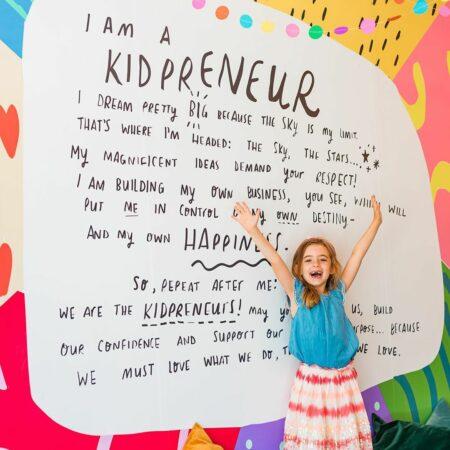 kidpreneur in front of the kidpreneur pledge wall
